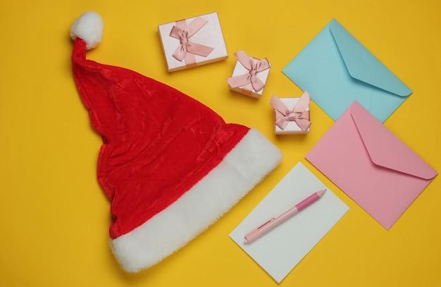 Lettre au père noël. bonnet de noel, enveloppe avec lettre et stylo, boîtes de cadeaux sur fond jaune. noël à plat. vue de dessus