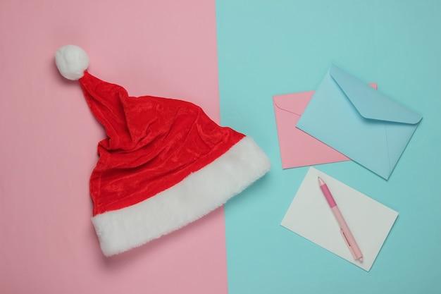 Lettre au père noël. bonnet de noel, enveloppe avec une lettre et un stylo sur fond bleu rose. noël à plat. vue de dessus