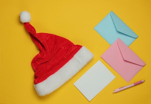 Lettre au père noël. bonnet de noel, enveloppe avec une lettre et un stylo sur fond jaune. noël à plat. vue de dessus