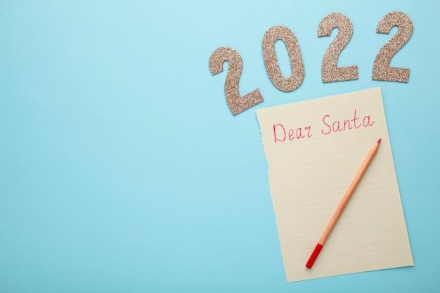 Lettre au père noël avec le numéro 2022 sur fond bleu. inscription cher père noël. vue de dessus