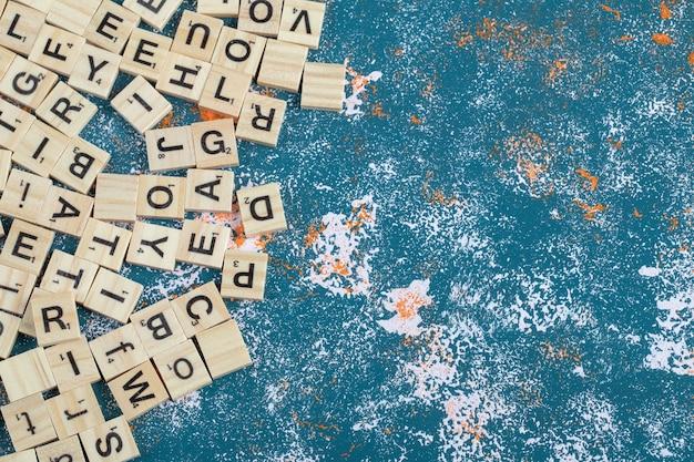 Dés de lettre en bois sur table bleue.