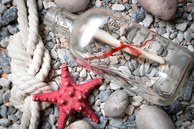 Lettre en bouteille sur pierres avec étoile de mer rouge et noeud marin
