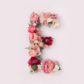 Lettre e faite de vraies fleurs et feuilles naturelles. concept de police de fleur. collection unique de lettres et de chiffres. idée créative pour le printemps, l'été et la saint-valentin.