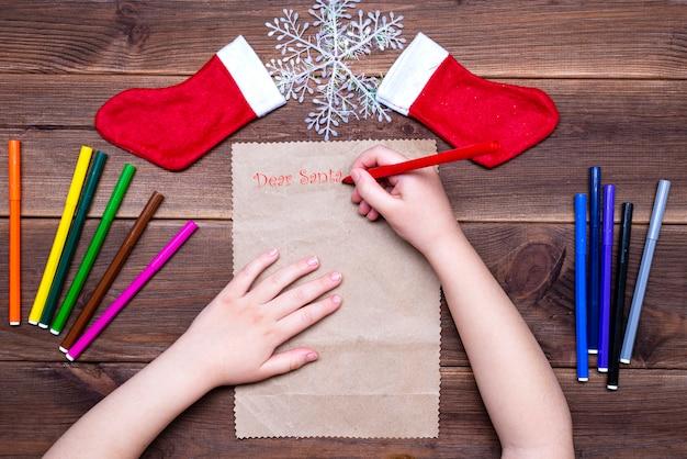 Lettre des enfants au père noël. petite fille écrit une lettre avec des feutres multicolores sur une table en bois