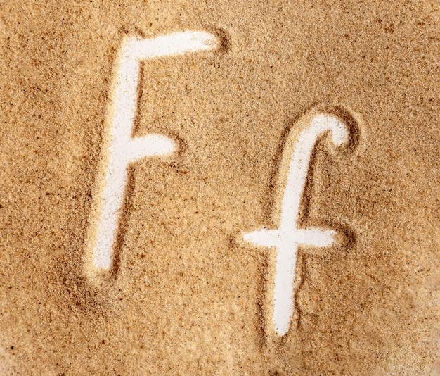 Lettre f alphabet manuscrit anglais dans le sable