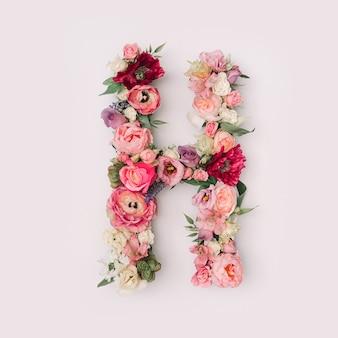 Lettre h faite de vraies fleurs et feuilles naturelles. concept de police de fleur. collection unique de lettres et de chiffres. idée créative pour le printemps, l'été et la saint-valentin.