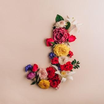 Lettre j faite de vraies fleurs naturelles sur fond beige. police de fleur. concept créatif d'été. vue de dessus. mise à plat