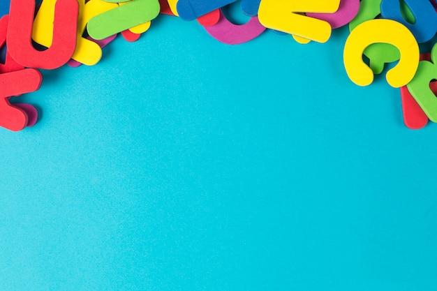 Lettre multicolore ordre aléatoire fond plat lay