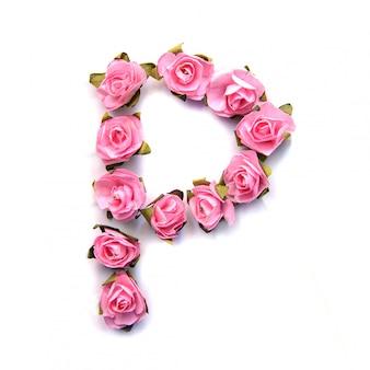 Lettre p de l'alphabet anglais de roses roses sur une surface blanche