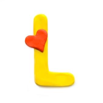 Lettre de pâte à modeler jaune l alphabet anglais avec coeur rouge qui signifie amour