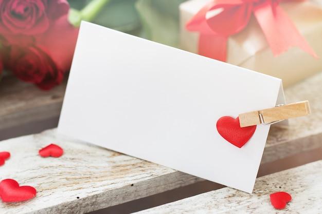 Lettre avec une pince et un coeur rouge avec des roses à côté