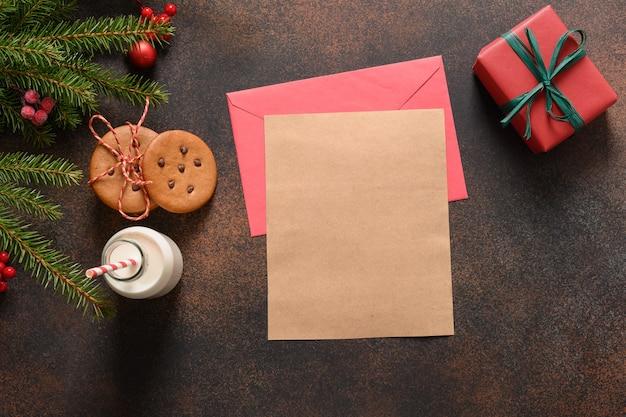 Lettre pour le lait du père noël et les biscuits faits maison sur l'espace de fond brun foncé pour le style plat de texte