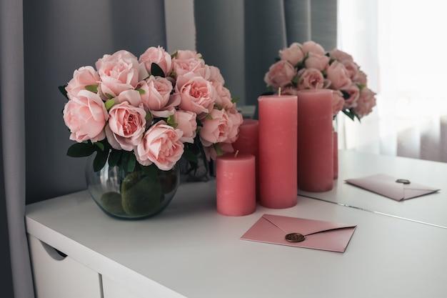 Lettre rose sur un bureau féminin, un bouquet de roses et de bougies.