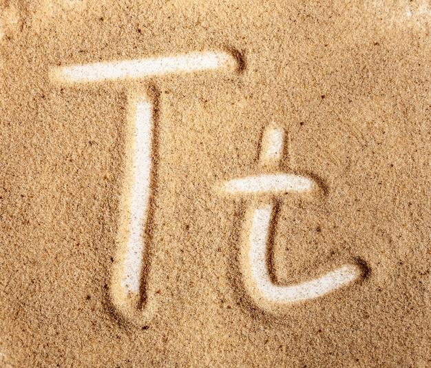 Lettre t alphabet manuscrit anglais dans le sable