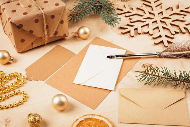 Lettre de voeux, enveloppe et plume entourées de décorations de noël