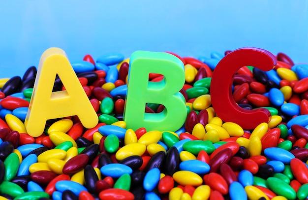 Lettres abc colorées sur des bonbons colorés. apprenez des langues étrangères.