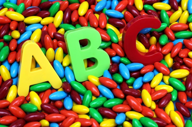 Des lettres abc colorées sont placées sur des bonbons colorés. anglais pour les débutants.