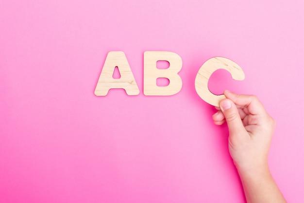Lettres abc dans les mains de l'enfant sur fond rose