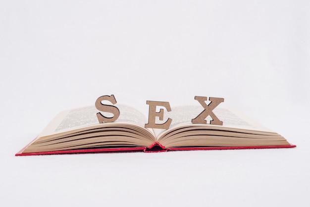 Lettres abstraites de mot sexe, livre ouvert fond blanc