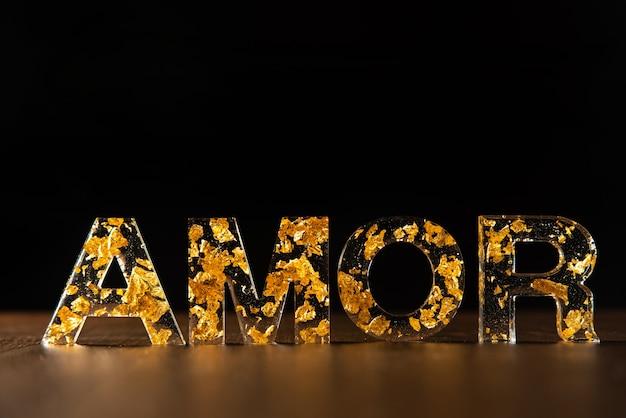 Lettres acryliques avec des feuilles d'or formant le mot amour en portugais sur une surface en bois, fond noir, mise au point sélective.
