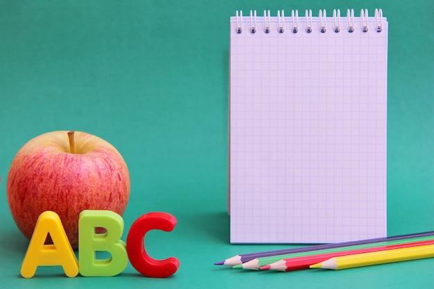 Lettres de l'alphabet anglais abc à côté de la pomme. crayons de couleur et une page de bloc-notes vide