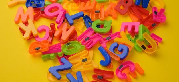 Lettres de l'alphabet anglais en plastique multicolore avec aimant sur surface jaune, bannière