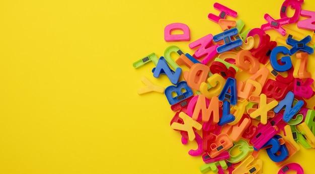 Lettres de l'alphabet anglais en plastique multicolore avec aimant sur surface jaune