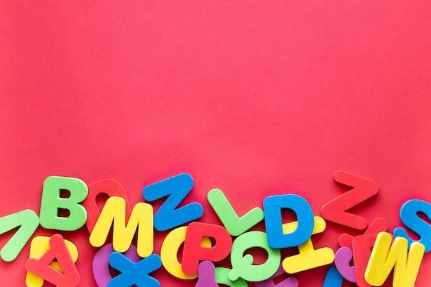 Lettres de l'alphabet en différentes couleurs sur fond rouge. étude de l'alphabet, abc, concept de l'éducation