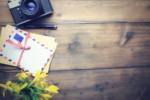 Lettres, appareil photo, stylo et fleur sur table en bois