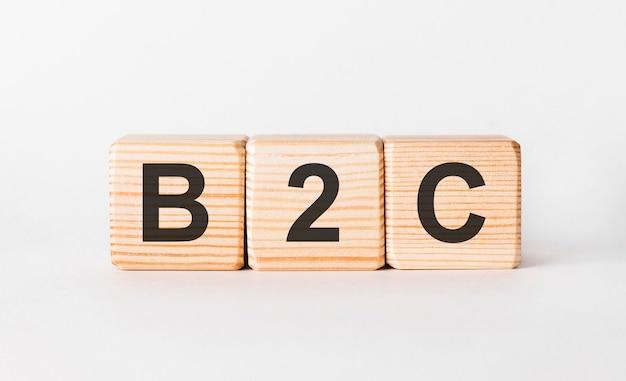 Lettres b2c de blocs de bois en forme de pilier sur blanc, copiez l'espace