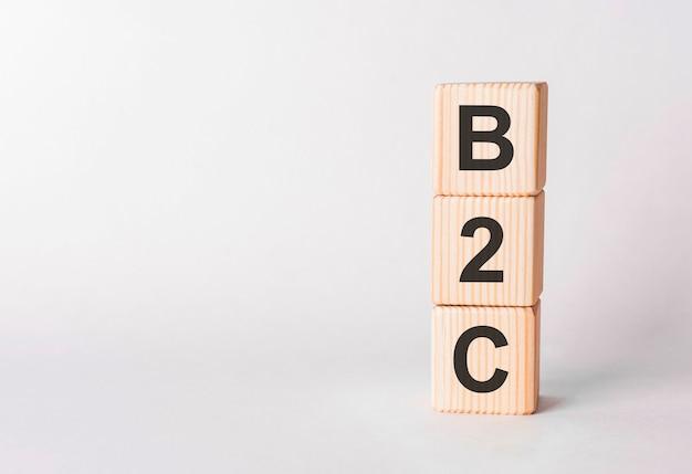 Lettres b2c de blocs de bois en forme de pilier sur fond blanc, copiez l'espace