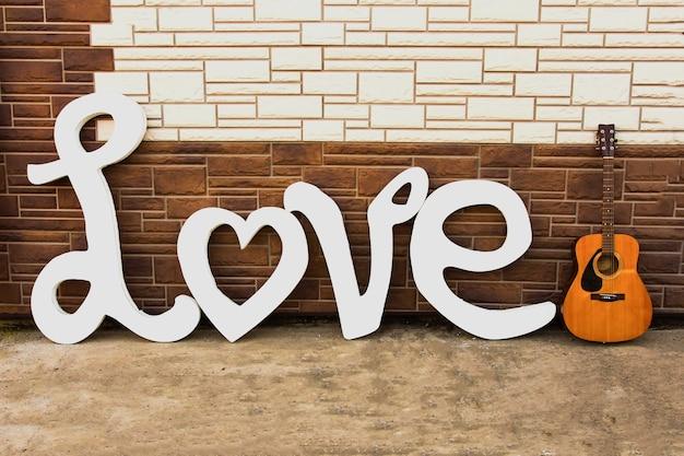 Lettres blanches en bois formant le mot amour avec une guitare acoustique en bois, sur fond de briques claires et sombres.