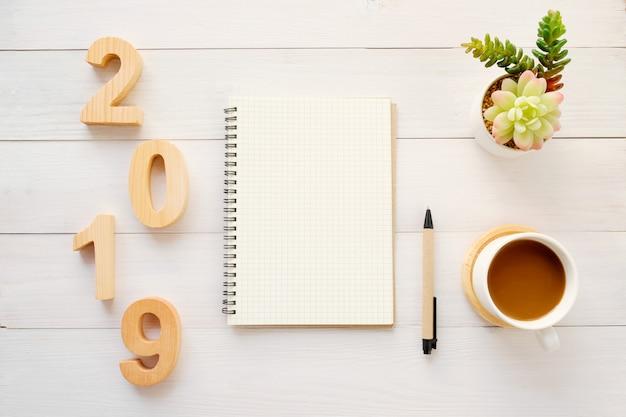 Lettres de bois 2019, papier de cahier vierge et café sur fond de tableau blanc