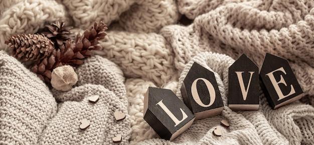 Les lettres en bois composent le mot amour sur fond d'articles tricotés douillets. concept de vacances de la saint-valentin.