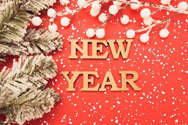 Lettres en bois dans une casquette du nouvel an sur fond rouge avec des branches d'épinette verte et de la neige.