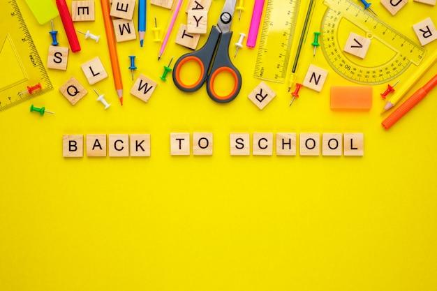 Lettres en bois disposées en phrase retour à l'école et fournitures de bureau sur jaune, copiez l'espace