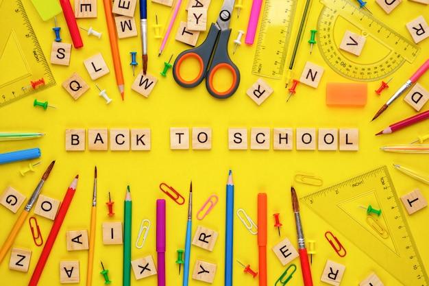 Lettres en bois disposées en phrase retour à l'école et fournitures de bureau sur jaune