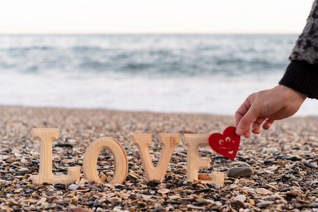 Lettres en bois formant le mot amour et une main tenant un coeur rouge au bord de la mer. concept de st. la saint-valentin