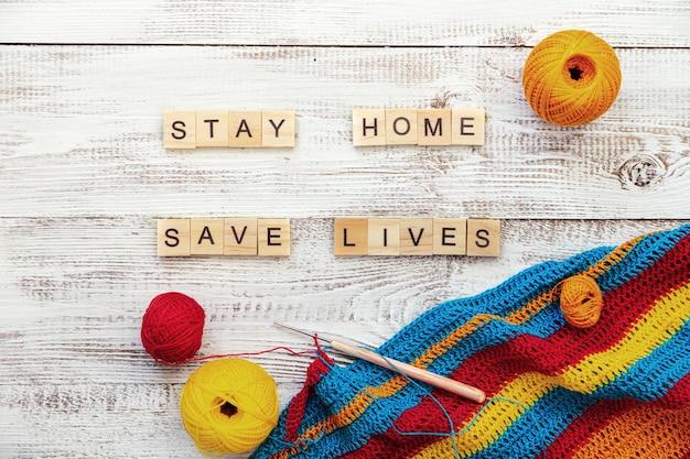 Les lettres en bois forment l'expression «restez à la maison, restez en sécurité». matériel de tricot et de dessin, désordre créatif. concept d'auto-isolement, de coronavirus et de pandémie.