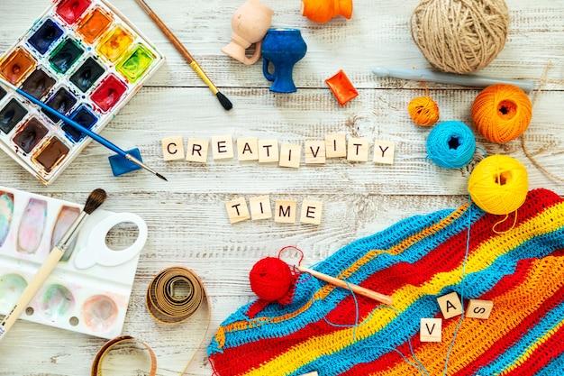 Les lettres en bois forment l'expression «temps de créativité». matériel de tricot et de dessin, désordre créatif. rester à la maison.