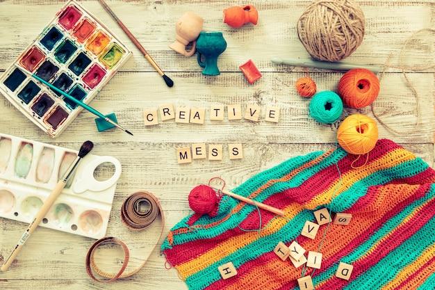 Lettres en bois avec matériel de tricot et de dessin, désordre créatif. restez à la maison, soyez en sécurité.