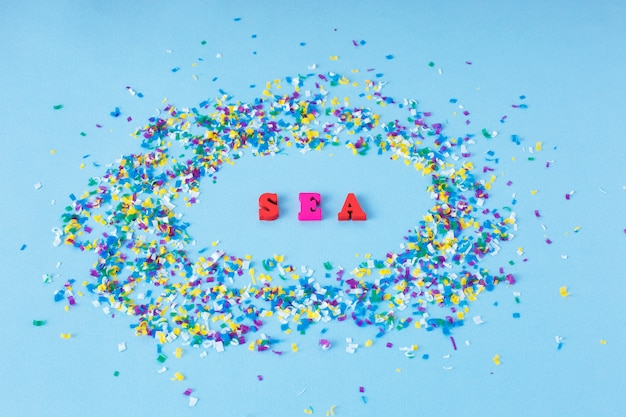 Lettres en bois avec le mot mer autour de particules de microplastique sur un fond bleu.