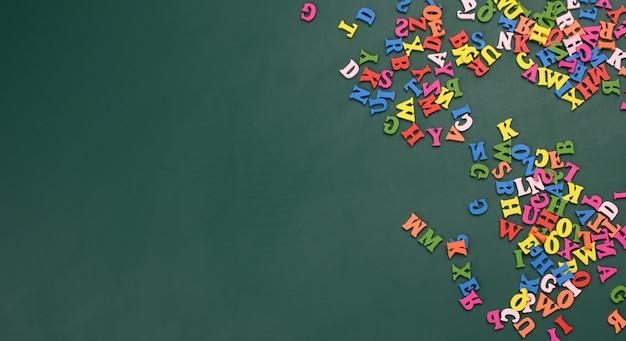 Lettres en bois multicolores de l'alphabet anglais sur fond vert, copie sace