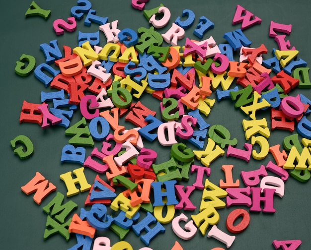 Lettres en bois multicolores de l'alphabet anglais sur une surface verte, gros plan