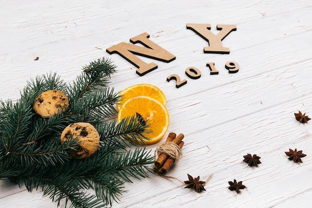 Les lettres en bois «ny 2018» se trouvent sur le sol entourées de biscuits, de branches de sapin, d'épices et d'oranges