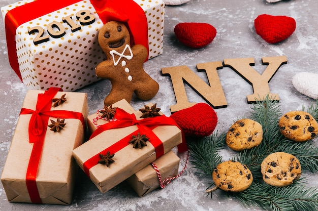 Les lettres en bois «ny 2019» se trouvent sur le sol entourées de biscuits, de branches de sapin et de boîtes présentes