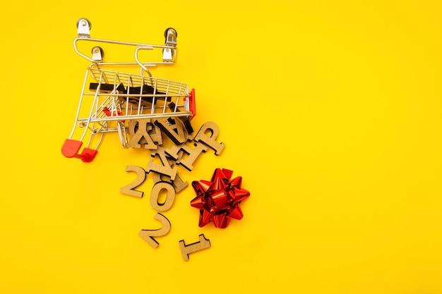 Des Lettres En Bois Sont Tombées D'un Chariot D'épicerie Avec Un Arc D'emballage Rouge Sur Fond Jaune. Photo Premium