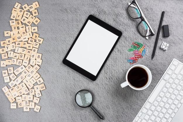 Lettres en bois; tablette numérique; tasse à café et fournitures de bureau sur fond gris