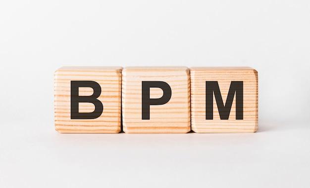 Lettres bpm de blocs de bois en forme de pilier sur blanc