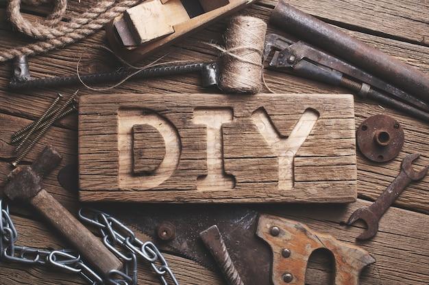 Lettres de bricolage sur une planche de bois sur le fond d'outils de travail
